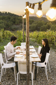 Italy, Tuscany, Siena, young couple having dinner in a vineyard - FBAF00213
