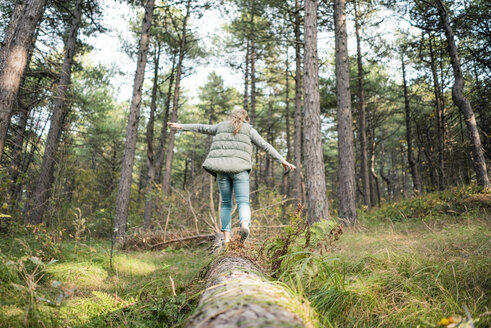 Little girl balancing on a tree trunk in the forest - MOEF01568
