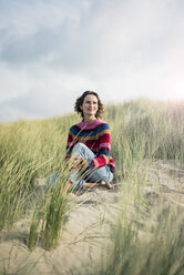 Mature woman relaxing on the beach, sitting in the dunes - MOEF01574