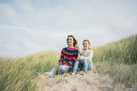 Mother and daughter sitting on a beach dune, girl pointing at distance, smiling - MOEF01580