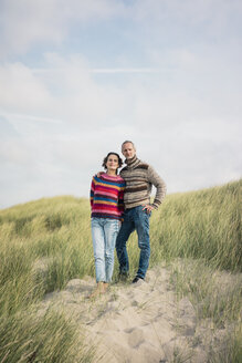 Mature couple standing in the dunes, with arms around - MOEF01583