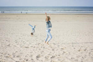 Mother and daughter having fun, cartwheeling on the beach - MOEF01586