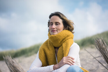 Mature woman relaxing in the dunes, enjoying the wind - MOEF01592
