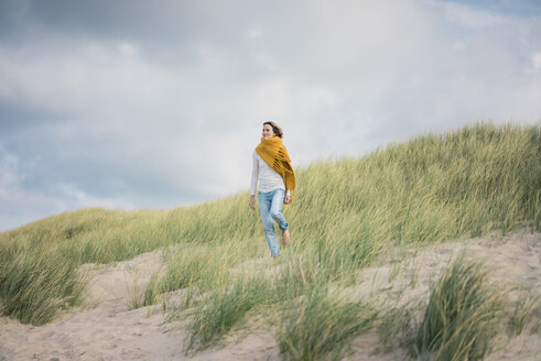 Mature woman relaxing in the dunes, enjoying the wind - MOEF01595