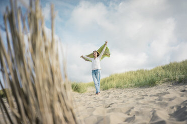 Mature woman holding flapping scarf in the wind, relxiang in the dunes - MOEF01598