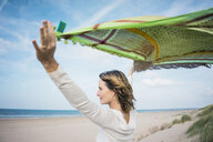 Mature woman holding flapping scarf in the wind, relxiang in the dunes - MOEF01601