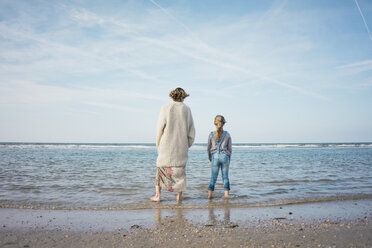 Mother and daughter standing on the beach, looking at the sea, rear view - MOEF01607