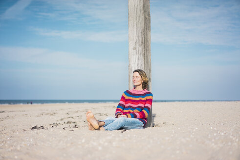 Mature woman relaxing on the beach, leaning on a pole - MOEF01613