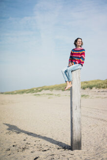 Mature woman sitting on a wood pole on the beach - MOEF01616