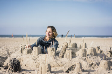 Mature woman building a sandcastle on the beach - MOEF01622