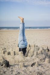 Mature woman doing a headstand on the beach in a sandcastle - MOEF01625