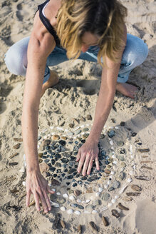 Mature woman making a heart from seashells on the beach - MOEF01628
