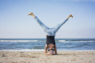 Mature woman doing a headstand on the beach - MOEF01631