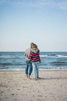 ture couple standing on the beach with arms around, looking at the sea - MOEF01634