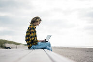 Mature woman sitting on boardwalk at the beach, using laptop - MOEF01637