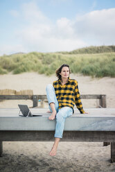 Mature woman sitting on boardwalk at the beach, using laptop - MOEF01640