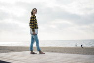 Mature woman standing on boardwalk at the beach, holding laptop - MOEF01643