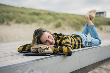 Mature woman with laptop, lying on boardwalk at the beach, relaxing - MOEF01646
