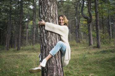 Woman hugging tree in forest - MOEF01649