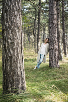 Serene woman standing in the forest - MOEF01652
