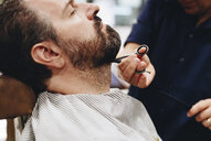 Midsection of barber cutting man beard at salon - CAVF56022