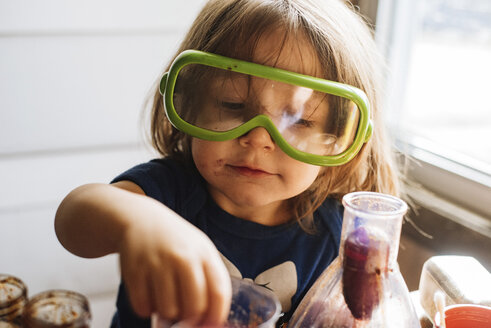 Close-up of girl wearing protective eyewear while holding food at home - CAVF56097