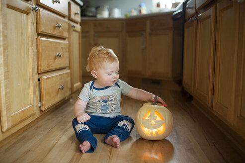 Cute baby boy with jack o' lantern sitting on floor in kitchen - CAVF56100