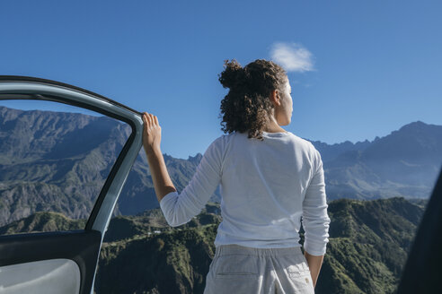 Rear view of woman standing by car against mountains during sunny day - CAVF56121