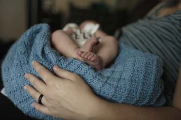 Midsection of mother with newborn son at home - CAVF56142