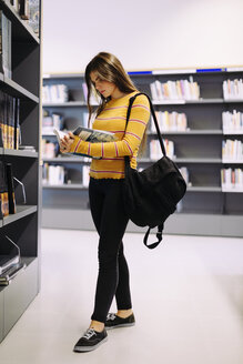Woman with backpack reading book while standing in library - CAVF56172