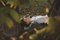 High angle view of thoughtful boy lying at park seen through branches - CAVF56205