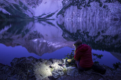 High angle view of female hiker using headlamp while making coffee by lake against mountains - CAVF56301