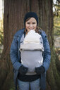 Portrait of cheerful mother carrying newborn son in baby carrier against tree trunk at park - CAVF56388