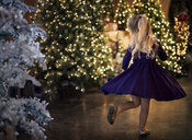 Rear view of happy girl dancing by illuminated Christmas trees at night - CAVF56391