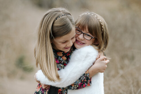 Happy sisters embracing while standing on field - CAVF56436