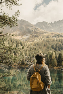 Switzerland, Engadin, woman on a hiking trip standing at lakeside in mountainscape - LHPF00133