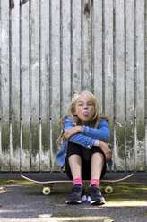 Portrait of girl sitting on skateboard in front of wooden wall sticking out tongue - JFEF00918