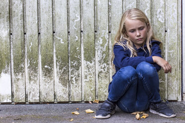 Portrait of sad girl sitting in front of wooden wall - JFEF00939
