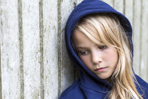 Portrait of sad blond girl wearing blue hooded jacket leaning against wooden wall - JFEF00942