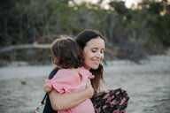 Australia, Queensland, Mackay, Cape Hillsborough National Park, happy mother hugging her daughter at the beach - GEMF02579