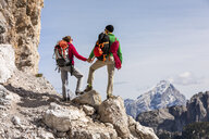 Italy, Cortina d'Ampezzo, couple with rope and climbing equipment holding hands and looking at view - WPEF01136