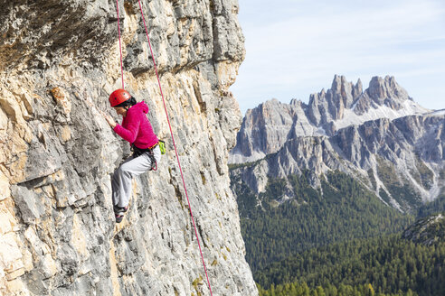 Italy, Cortina d'Ampezzo, woman climbing in the Dolomites mountains - WPEF01145
