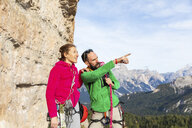 Italy, Cortina d'Ampezzo, couple with climbing equipment looking at view an talking in the Dolomites mountains - WPEF01157