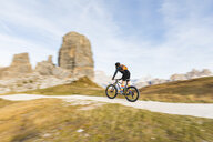 Italy, Cortina d'Ampezzo, panning view of man cycling with mountain bike in the Dolomites mountains - WPEF01163