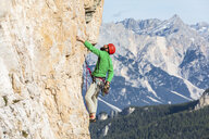 Italy, Cortina d'Ampezzo, man using chalk powder while climbing in the Dolomites mountains - WPEF01169