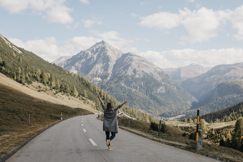 Switzerland, Engadin, rear view of happy woman with raised arms on mountain road - LHPF00149