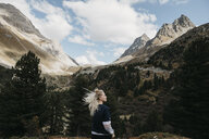 Switzerland, Grisons, Albula Pass, young woman with windswept hair standing in mountainscape - LHPF00152