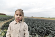 Portrait of a girl standing on a cabbage field - KMKF00662