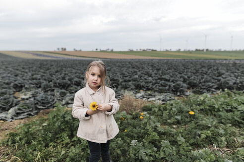 Portrait of a girl standing at a cabbage field holding a flower - KMKF00668