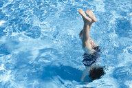 Little girl doing handstand in swimming pool - ERRF00156